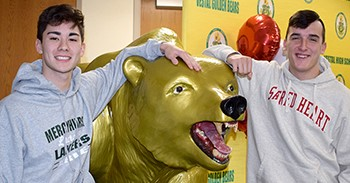 Vestal Golden Bear Lacrosse teammates Jared Butler and Matt Thrasher stand on either side of the Golden Bear statue following their National Letters of Intent signing ceremony on November 28, 2018