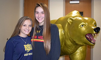 Field Hockey teammates at Vestal High School, Sydney Washburn and Makayla Kintner stand next to the Vestal Golden Bear statue before their national letter of intent joint signing ceremony in the Vestal High School lobby on December 13, 2018