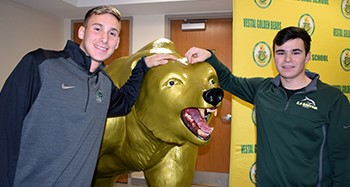 Dan Mansfield and Luke Barney pose on each side the Vestal Golden Bear statue after their joint letter of intent signing in the Vestal High School lobby on December 5, 2018