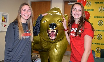 Caitlin and Sarah Harding flank the Vestal Golden Bear statue in the Vestal High School lobby for their moment in the spotlight prior to their National Letter of Intent joint signing ceremony on January 22, 2019.