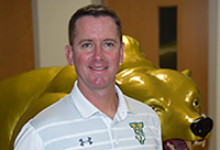 Vestal Central School District's new Director of Athletics and Physical Education Josh Gannon by the Vestal Golden Bear.
