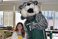 A second-grade girl at Clayton Avenue Elementary School stands next to Baxter the Bearcat from Binghamton University in her classroom.
