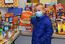 A second-grade boy in blue jacket and mask sets a box of Pumpkin Spice Cheerios on the table with other food donations.