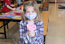 Glenwood first-grade girl holds a pink Valentine heart she decorated for a Vestal Park resident.