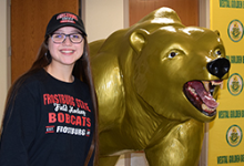 Gabrielle Rosas, in Frostburg State University hoodie and baseball hat, stands next to the Vestal Golden Bear statue.