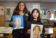 Two Vestal High School tenth-grade art students, both girls, hold portraits they created of refugee children in Malaysia as part of The Memory Project.