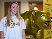 Samantha Schaffer, Vestal Golden Bear Field Hockey player, stands next to the Vestal Golden Bear in the Vestal High School lobby right before she signs her letter of intent with Division 2 Bloomsburg University