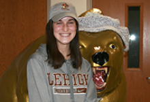 Simone Davey, Vestal High School senior and Golden Bear track athlete, wears a gray Lehigh University hoodie and baseball hat as she stands next to the Golden Bear statue in the school lobby before her letter of intent signing on December 20, 2019.