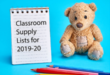 Stuffed Teddy Bear next to a stenographer's notebook propped open to a page that says Classroom Supply Lists for 2019-20; in the foreground a few colored pencils are laying on the table.