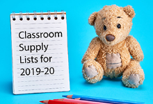Brown stuffed teddy bear sitting next to a steno pad with the words Classroom Supply Lists for 2019-20 written on it. In the foreground lay some colored pencils.