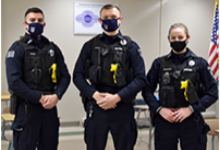 Vestal Police officers Perez, Mabee and Chapman stand shoulder to shoulder in their uniforms and masks.