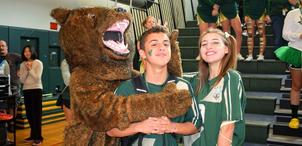"""Timber,"" the Vestal Golden Bear mascot, puts the squeeze on a sophomore while another student does bunny ears behind his head. (Fall Pep Rally; 10/05/2017)"
