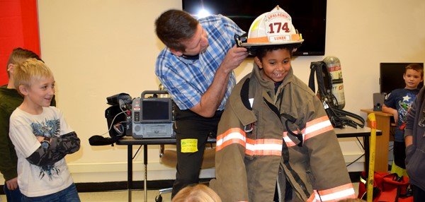 A boy gets to try on the firefighting gear during a Fire Safety lesson by the Apalachin Fire Department at Tioga Hills Elementary School.