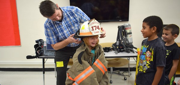 The Apalachin Fire Chief sets his helmet on a female student's head as she gets to try on the gear during a fire safety lesson at Tioga Hills Elementary School.