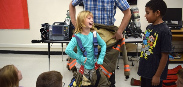 A Tioga Hills Elementary School student laughs with another student as she begins to try on the fire suit with help from the Apalachin Fire Dept. Chief.