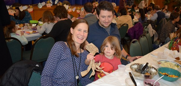 A mother and father enjoy the Thanksgiving Feast with their Universal Pre-Kindergarten student at the Jewish Community Center campus on November 15.