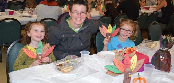 A mother and her two daughters, who are Universal Pre-Kindergarten students, attend the Thanksgiving Feast at the Jewish Community Center campus on November 15.