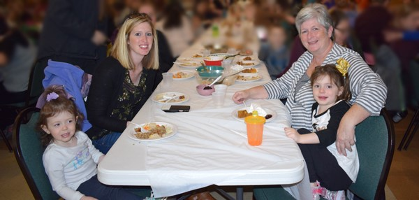 A mother and grandmother enjoy the Thanksgiving Feast with their Universal Pre-Kindergarten student and another daughter at the Jewish Community Center campus on November 15.