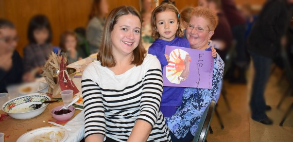 A Universal Pre-Kindergarten student enjoys the Thanksgiving Feast with her mother and grandmother at the Jewish Community Center campus on November 15.