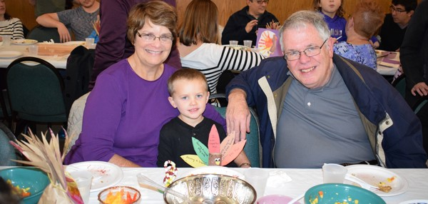Two grandparents have fun celebrating the Thanksgiving Feast with their grandson at the Jewish Community Center campus on November 15.