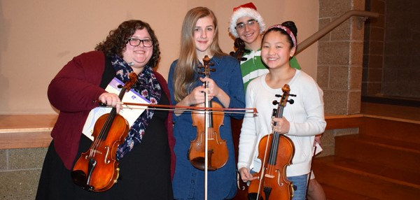 The Vestal Middle School grade 7/8 Orchestra teacher poses with three of her students after playing as a string quartet during the Holiday Concert on December 15, 2017.