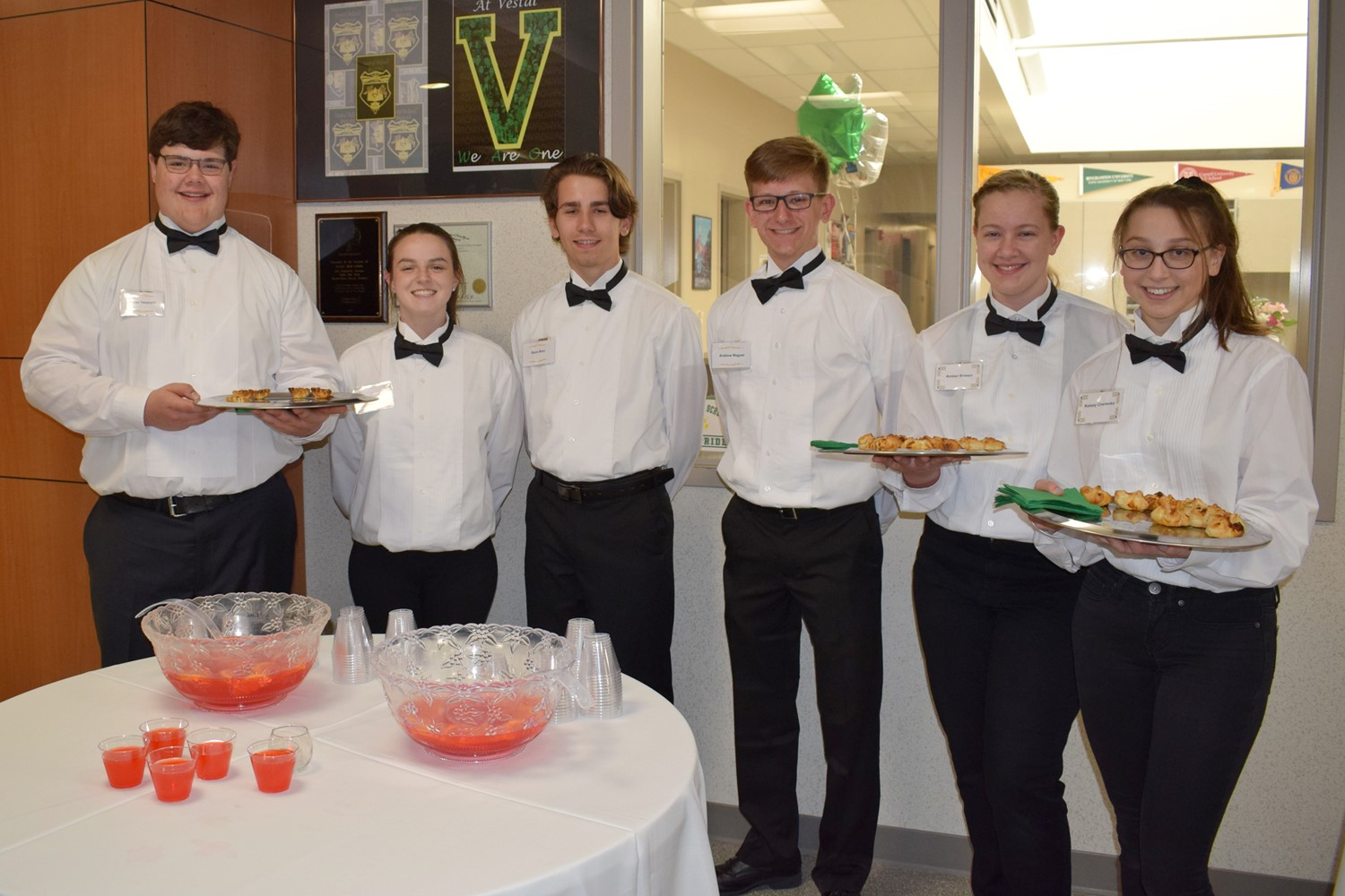 Student wait staff are ready to serve punch and delicious canapes during the reception.