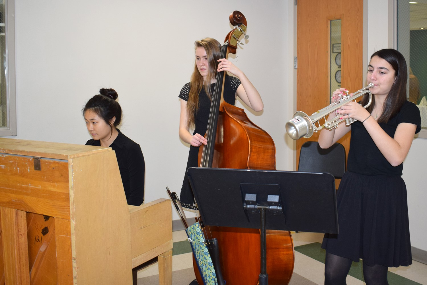 Three high school students play the piano, cello and trumpet during dinner.