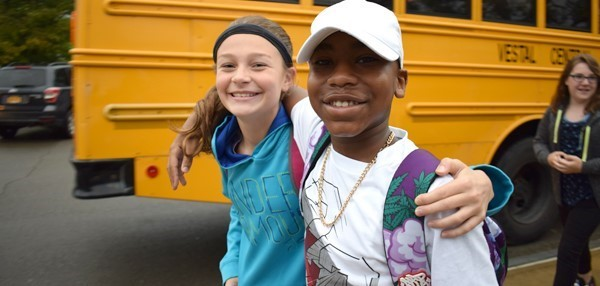 Two middle school students, girl and a boy, smile for the camera after coming off the school bus on the first day of school at Vestal Middle School.