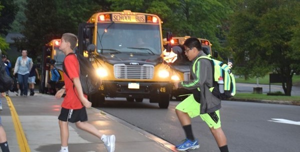 Two boys scoot across the bus loop in front of Vestal Middle School on the first day of school.