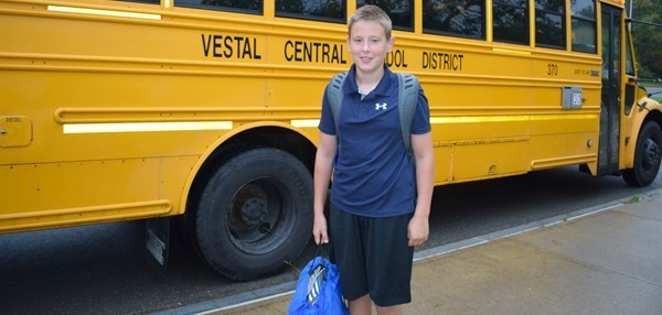 A boy poses with backpack in front of a school bus on the first day of school at Vestal Middle School.