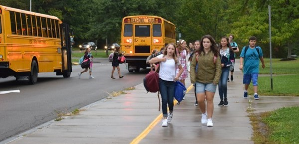 Vestal Middle School students stream up the sidewalk by the bus loop after getting off their buses on the first day of school.