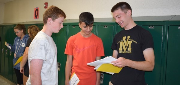 A Vestal High School student looks over the schedules of two ninth-graders he will be mentoring during the 2017-18 school year.