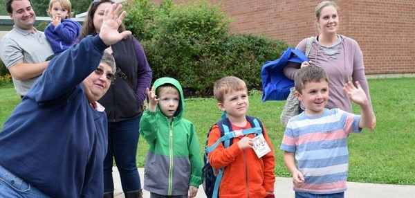 A school bus driver shows three boys how to wave to the bus driver after they have gotten off as part of school bus safety training during Kindergarten orientation at Tioga Hills Elementary