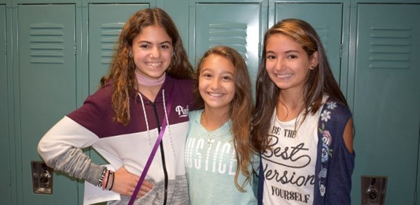 Three friends pose in front of their lockers at Vestal Middle School during sixth-grade orientation.