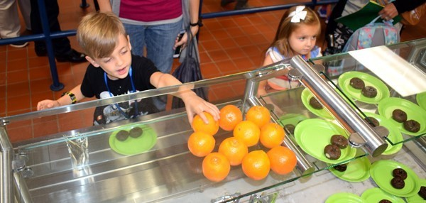 A boy reaches for an orange in the cafeteria line during Kindergarten Orientation at Vestal Hills Elementary.