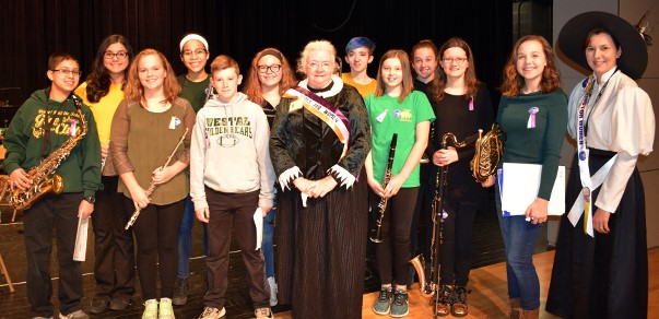 "Vestal Middle School Band students pose with the guest speaker dressed as Susan B. Anthony after they played ""The Suffragette Waltz"" during an assembly on December 8, 2017."