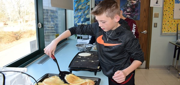 A Vestal Middle School boy prepares to flip a pancake on a griddle in the Family and Consumer Science classroom during a cooking workshop on Student Activity Day, December 8, 2017.
