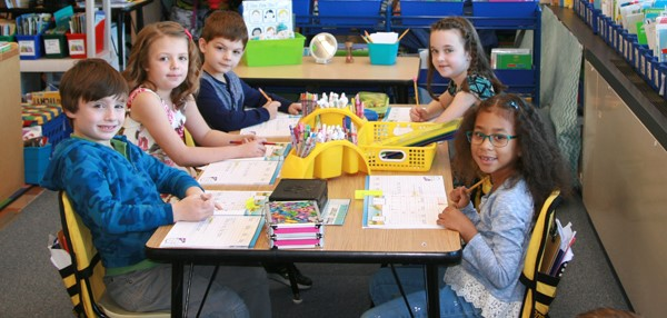 Clayton Avenue Elementary School first-graders sit together at a table while working on a classroom project.