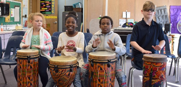 Four Clayton Avenue Elementary School third-graders, two boys and two girls, enjoy playing on the African drums in the school's music room.