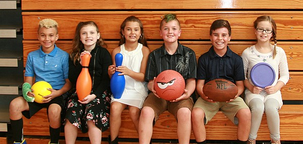 Six Clayton Avenue Elementary fifth-grade students sit on the bleachers in gym class, holding various physical education class equipment such as a football, basketball, frisbee and plastic bowling pins.