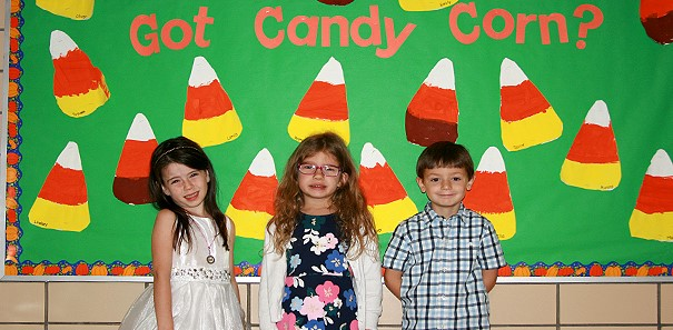 "Three Clayton Avenue Elementary Kindergarten students pose in front of a bulletin board in the hallway that asks ""Got Candy Corn?"" and is decorated with white, orange, yellow and brown paper candy corns."