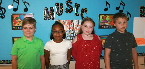 Clayton Avenue Elementary School fourth-graders, two boys and two girls, pose in front of a bulletin board decorated with a Music theme.