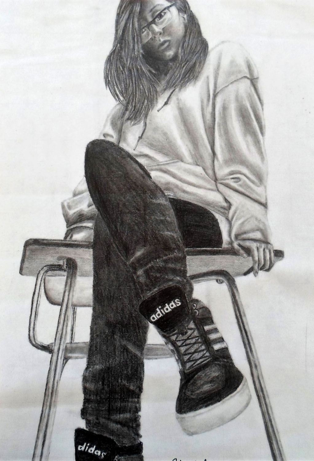 A black and white self portrait of a teenage girl sitting in a school desk from the perspective of t