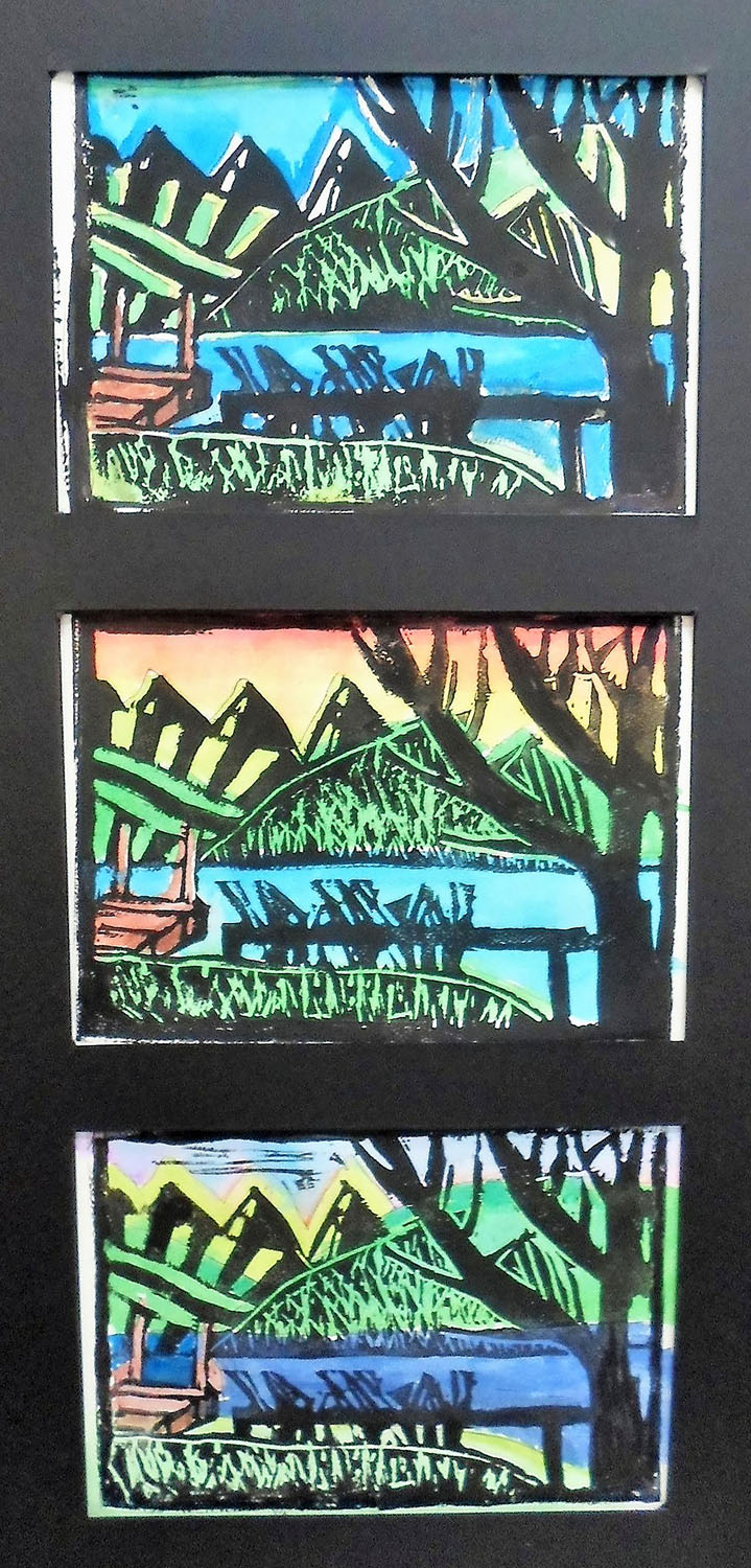 Three-part study of trees, mountains and a dock by a lake. All three views are in color.