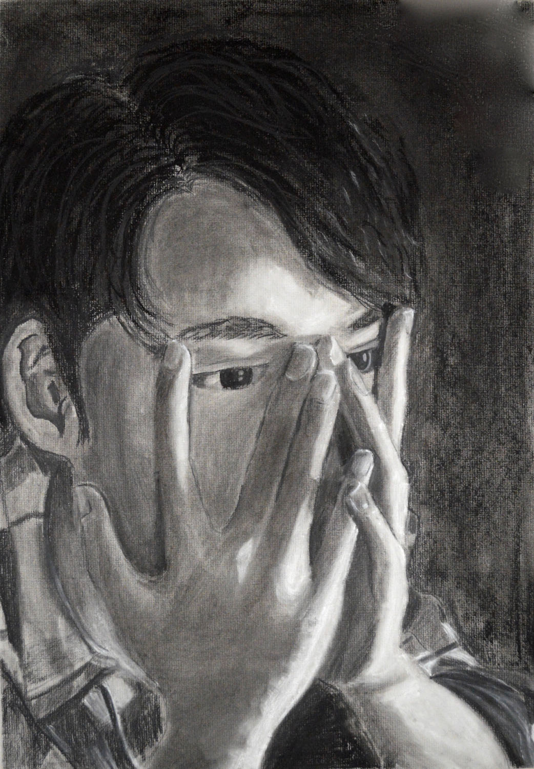 Black and white self portrait of a distraught-looking young man holding his face in his hands.