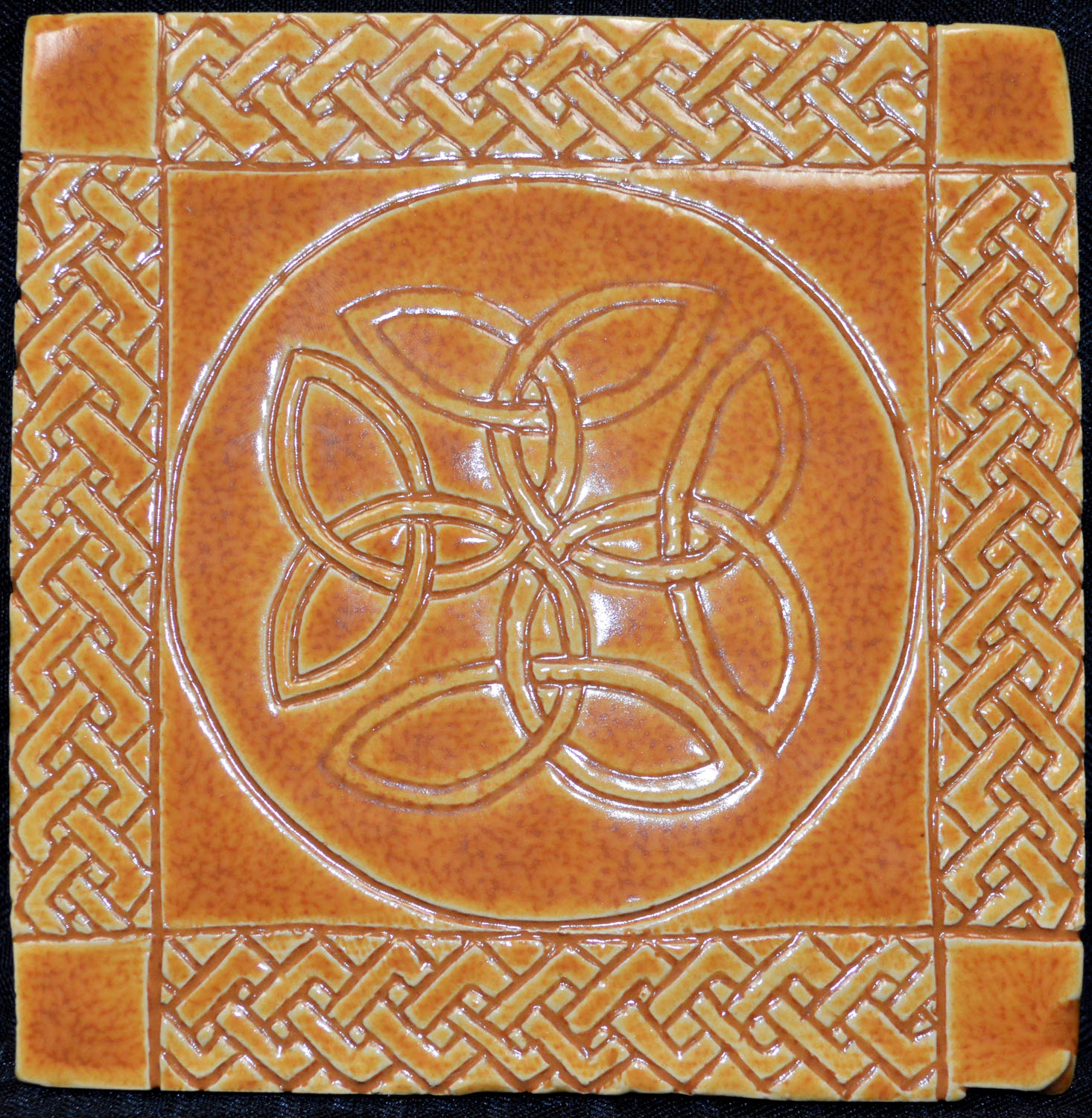 An orange ceramic tile with a Celtic-type design in the center, framed by a braided design around ea