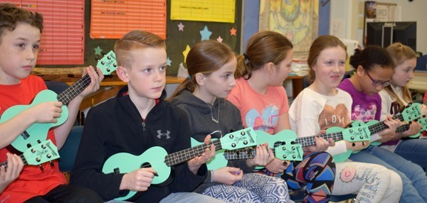 A group of fourth-graders learn the notes on their light green ukuleles.