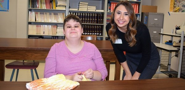 Senior Aspen Poole knits a dish cloth as she poses for a photo with local WBNG-TV news personality Chloe Vincente.