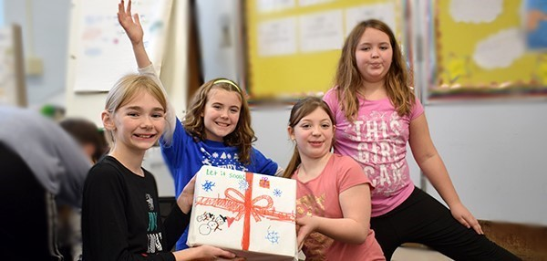 Four fifth-grade girls proudly display the box of personal care items they filled, wrapped and decorated as part of their grade-level Community Box Project