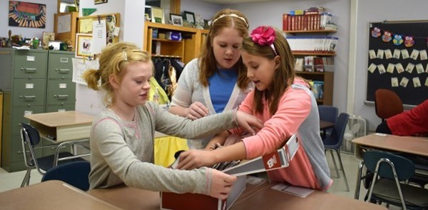 Three fifth-grade girls carefully pack personal care items into a shoe box as part of the Tioga Hills Elementary School's Fifth-grade Community Box Project to benefit patrons of the Apalachin Food Pantry